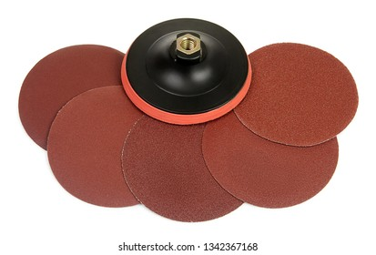 Set of round sandpaper discs with different grain types and plastic bracket handle with velcro tape strips for grinding machine isolated on white background. Serie of tools. Top view.