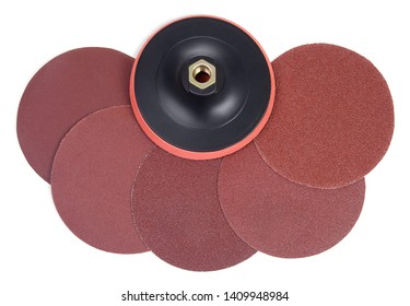Set of round sandpaper discs with different grain types and plastic bracket handle with velcro tape strips for grinding machine isolated on white background. Top view.