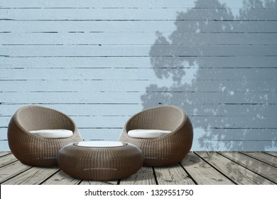 A set of round wicker chairs on old wooden deck with background of old wood wall panel with shadow of tree leaves. Copy space.