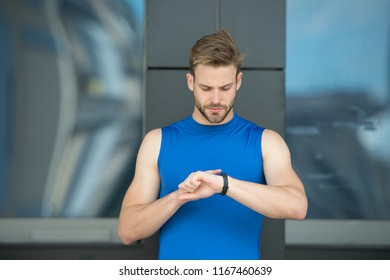 Set up route. Man athlete busy face check fitness tracker urban background. Athlete with bristle looks at fitness tracker or pedometer. Sportsman training with pedometer gadget. Sport gadget concept.