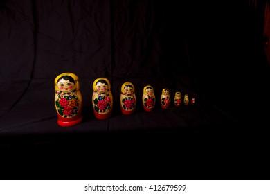 Set of Russian Dolls matryoshka in row, on black background.