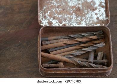 A set of rusty drill bit in a metal rusty box.