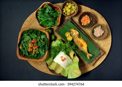 A set of Sabah people cuisine - linopot (rice) tuhau (local ginger), nonsom tipun (small prawn), fried white chili, and chayote young leaves stir fry and salted fish. Simple and healthy local food.