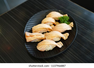 Set of salmon aburi sushi on wooden table background, Aburi style refers to nigiri sushi, the fish is partially grilled topside and partially raw, Traditional Japanese Food.