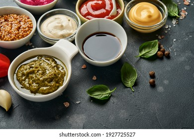 Set of sauces in bowls - ketchup, mayonnaise, mustard, soy sauce, bbq sauce, pesto, chimichurri, mustard grains on dark stone background. Top view copy space.
