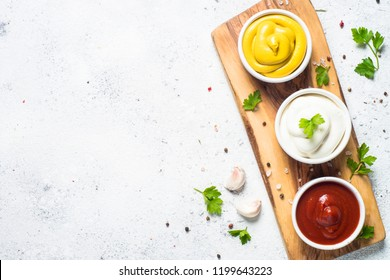 Set of sauces - ketchup, mayonnaise and mustard on white background. Top view.