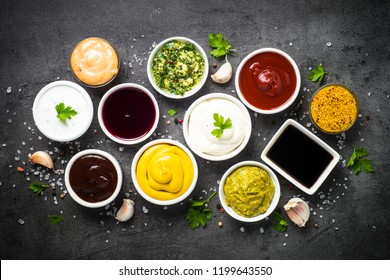 Set of sauces - ketchup, mayonnaise, mustard soy sauce, bbq sauce, pesto, chimichurri, mustard grains and pomegranate sauce on dark stone background.