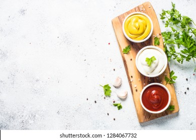 Set of sauces - ketchup, mayonnaise and mustard on white background. Top view on white.