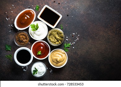 Set of sauces - ketchup, mayonnaise, mustard soy sauce, bbq sauce, pesto, mustard grains and pomegranate sauce on dark rusty stone or metal background. Top view copy space.