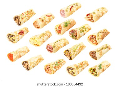 Set of savory stuffed crepes (Russian: blin, blini) decorated with herbs. Slavic cuisine. Isolated, shadowless