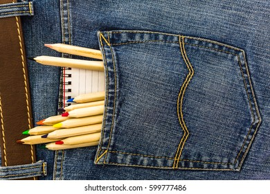 set of school pencils and small notebook in a back pocket of a blue denim jeans