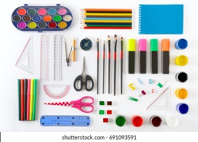 Set of school supplies on white background. Paint, pencils, notepad, brushes, scissors. Top view.