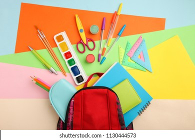 A set of school supplies scattered near a school backpack on a colorful background.