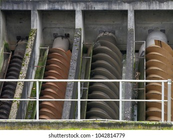 Set of screws of archimedes in a water pumping station. Set of screws of archimedes protected with fence in front.