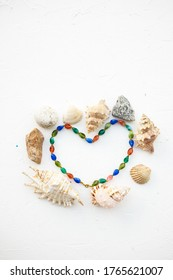 Set of seashells, pearls and stones in form heart on a  white background. Place for inscription. Postcard.