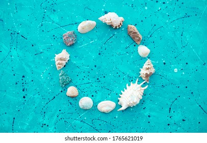 Set of seashells and stones in form circle on a beautiful blue background. Place for the inscription. Postcard.