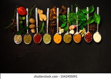 Set of seasoning in spoons on black background