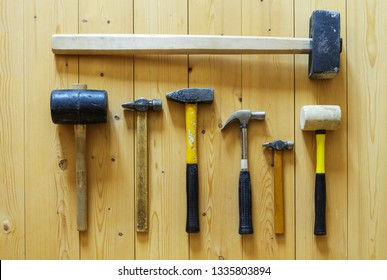 Set of seven old used hammers of different purposes, sizes and colors on wooden plank floor background