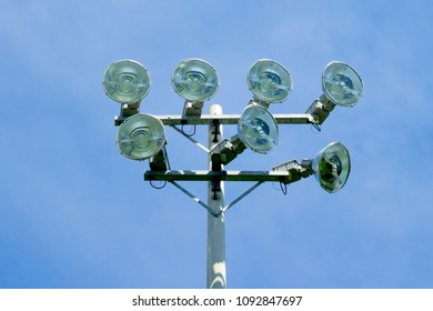 Set of seven powerful stadium floodlights on tower against blue sky.