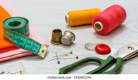 Set of sewing accessories. Sewing accessories for sewing: orange cloth, thimbles, spools of thread, tailor's scissors, a set of pins and a tape measure on a gray wooden table.