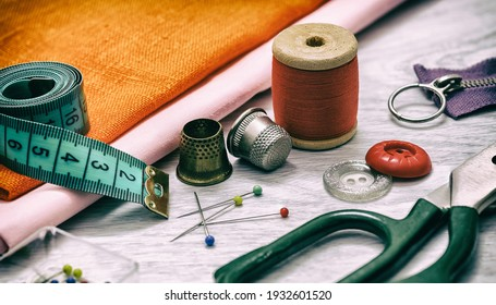 Set of sewing accessories. Sewing accessories for sewing: orange cloth, thimbles, spools of thread, tailor's scissors, a set of pins and a tape measure on a gray wooden table. retro style
