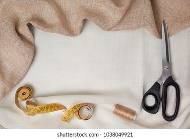 set for sewing. fabric, scissors, measuring tape, thread on light fabric. view from above