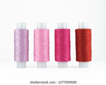 Set of sewing threads beautiful color (red, crimson, pink and lilac) on white  background with space for text, shadow of pink sewing accessories.