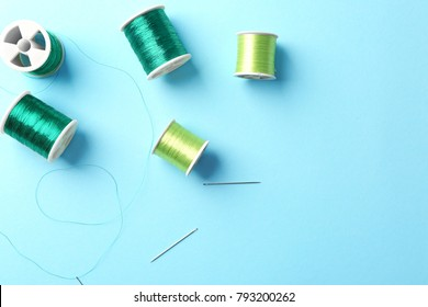 Set of sewing threads with needles on color background, top view