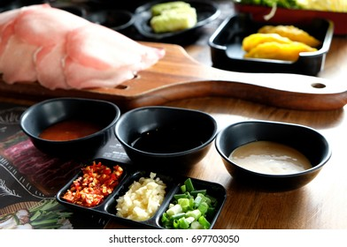 Set of shabu shabu Japanese hot pot food on wooden table including vegetables, sliced pork, chopped chili, garlic, spring onion, served with variety of sauce, sesame, Korean style, dumpling