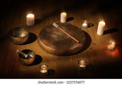 The set of Shaman tambourine, Tibetan bowl and candles in a dark room