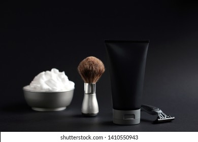 Set of shaving equipment and men's cosmetic products on black background
