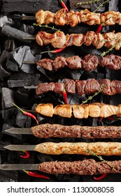 Set of Shish Kebabs or Barbecue Shashlik Collection on Charcoal Background with Herbs and Spices. Skewered Grilled Cubes Mix of Poultry Chicken Meat, Salmon Fish, Beef and Lamb Top View