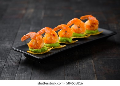 set of shrimps on tortilla chips, served with guacamole