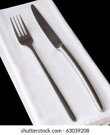 A set of silver knife and fork over a white napkin on a black table towel