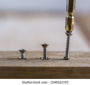 Set of silver screws screwed into timber wood on wooden top table background. One of them has screw driver on the screw.
