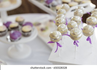 A set of silver and yellow glazed cake pops on sticks on a dessert stand at a party