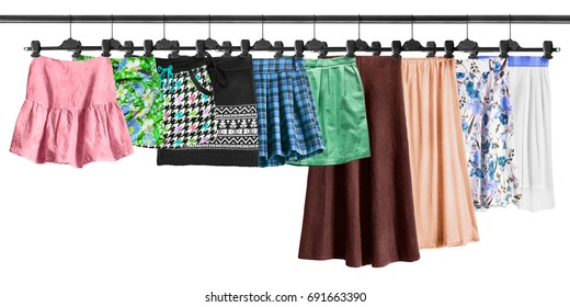Set of skirts hanging on clothes racks on white background