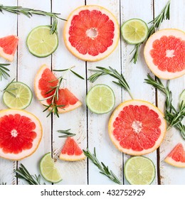 Set of sliced citrus lemon, lime, grapefruit, mint and rosemary on wooden background. View from above.