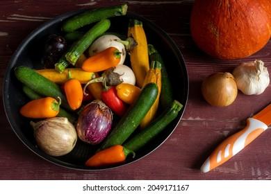 un ensemble de petits et grands légumes avec un couteau pour cuisiner sur une table en bois