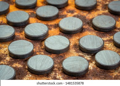 set of small round ceramic ferrite magnets - top view against rusty metal sheet