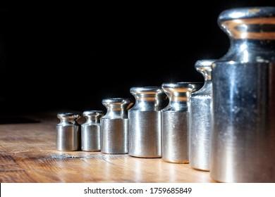kleine Gewichte für Schmuckwaagen auf einem Holztisch. Vorder- und Hintergrund unscharf mit Bokeh-Effekt