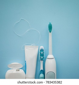 A set of sonic toothbrush, dental floss and toothpaste.