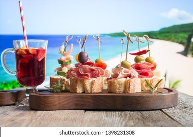 Set of Spanish tapas served on a sliced baguette with sangria on wooden table against the sea