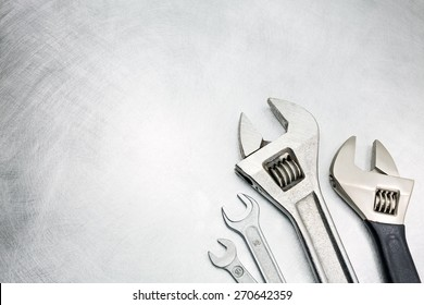 Set of spanners and wrenches on scratched metal background