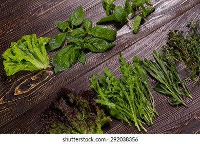 Set of spice herbs. Bunches of basil, rosemary,thyme, mint,arugula, salad iceberg on the wooden background.
