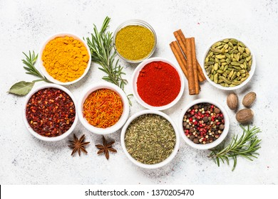 Set of spices in the bowls on white background. Curry, turmeric, peppercorn, paprika, basil, cinnamon, cardamom and other.