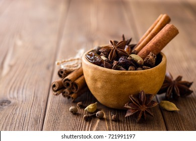 Set of spices for mulled wine in ceramic bowl on wooden table. Cinnamon sticks, star anise, cardamom, cloves, allspice and raisins. Selective focus.