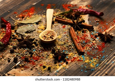 Set of spices on wooden background, close up. Wood spoon with dry spices, cinnamon sticks, anise stars and scattered seasoning. Cuisine and flavouring concept. Composition of condiment on sackcloth.