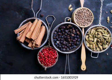 Set of spices over rustic metal background. Pink peppercorn, cardamom pods, juniper berries, coriander seeds and cinnamon sticks.