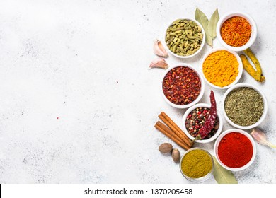 Set of spices over white stone table. Curry, turmeric, peppercorn, paprika, basil, cinnamon, cardamom and other.